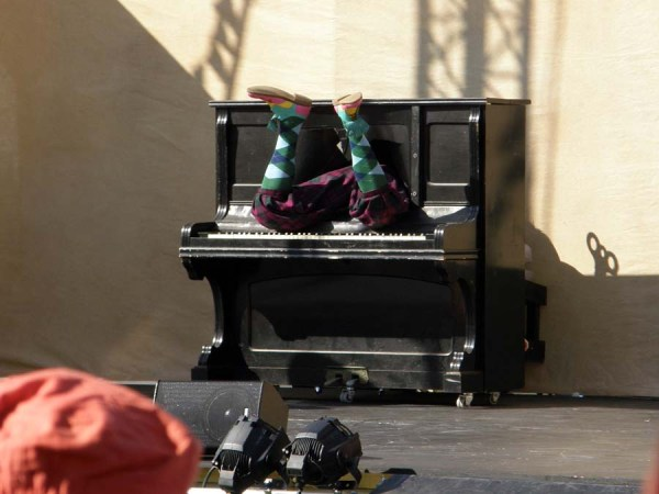Clown legs sticking out of a piano on theatre stage