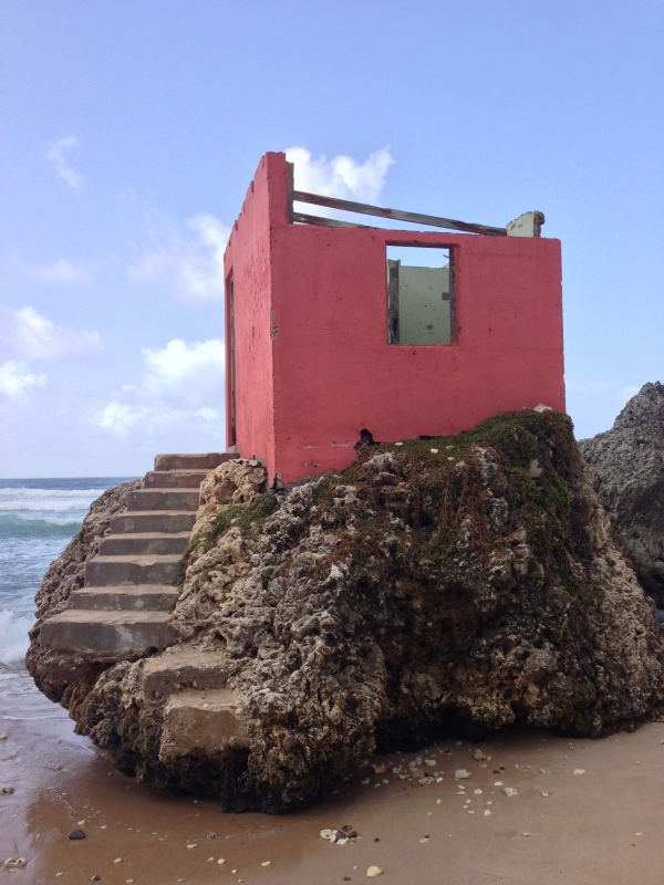 Roofless pink shack on beach