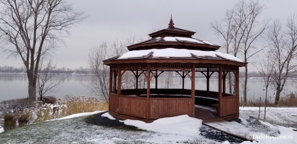 A gazebo sits on the snow covered banks of a large body of water.