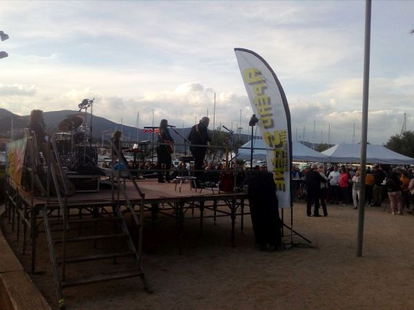 makeshift stage with band at a festival with tents