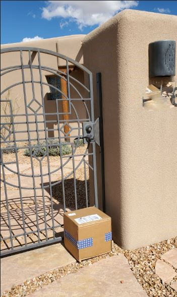 adobe house gate with a package sitting outside the gate