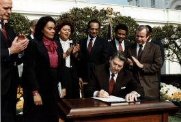 1280px-Reagan_signs_Martin_Luther_King_bill